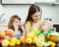 Woman with  daughters eating melon and peaches Royalty Free Stock Image