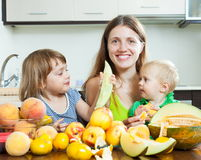 Woman with daughters eating peaches Stock Photos