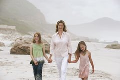 Woman And Daughters Walking On Beach Stock Photography