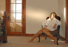 Woman daydreaming in chair. A view of a woman sitting in a fancy chair in the corner of a room as she relaxes or daydreams with light streaming from a nearby royalty free stock photos