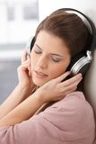 Woman daydreaming with headphone stock image