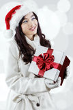 Woman daydreaming while holding a presents box Royalty Free Stock Image
