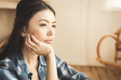 Woman daydreaming at home. Portrait of young engrossed woman daydreaming with hand on chin Stock Photo