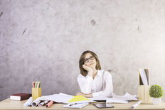Woman daydreaming in office. Attractive businesswoman daydreaming at office desktop with various items on concrete wall background Royalty Free Stock Images