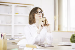 Woman daydreaming in office. Attractive european businesswoman holding notepad at chin while daydreaming in modern office with daylight Stock Photos