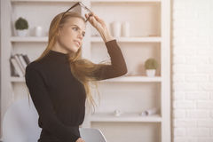 Woman daydreaming at workplace. Portrait of attractive young woman with glasses on head daydreaming in modern office Royalty Free Stock Images