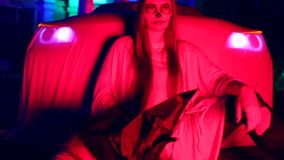 Woman with dead bride make-up for Halloween standing by the car in the white bride dress in the dark at abandoned house. The young woman with dead bride make-up stock video