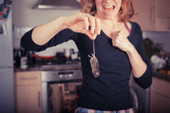Woman with dead mouse in kitchen Stock Image