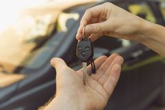 Woman dealer hand giving car keys to man, car on the background stock photos