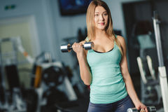 A woman deals with dumbbells in the gym. Strong woman weightlifting at the gym. Woman working out with dumbbells at a gym. Dumbbell bicep curl by a fitness girl Stock Images