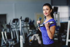 A woman deals with dumbbells in the gym. Strong woman weightlifting at the gym. Woman working out with dumbbells at a gym. Dumbbell bicep curl by a fitness girl Royalty Free Stock Photos