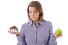 Woman debating cake or apple Royalty Free Stock Photos