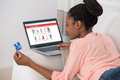 Woman With Debit Card Shopping Online. Young African Woman Shopping Online With Debit Card Royalty Free Stock Photo