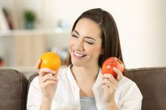 Woman deciding between different fruits. Happy woman deciding between different fruits sitting on a couch in the living room at home stock photos