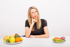 Woman deciding between healthy and unhealthy foods. Woman making  decision between healthy and unhealthy foods Stock Images
