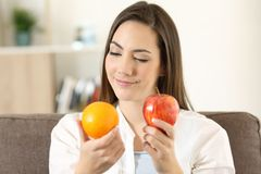 Woman deciding between an orange and apple. Front view portrait of a doubtful woman deciding between an orange and apple sitting on a couch at home Royalty Free Stock Photo