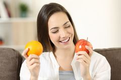 Woman deciding between orange and apple at home. Front view portrait of a happy woman deciding between orange and apple sitting on a couch in the living room at Stock Photo