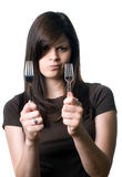 Woman deciding between plastic and reusable forks. A young woman deciding whether to use reusable silverware or plastic, disposable utensils Stock Photo
