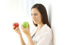 Woman deciding between red and green apples. Doubtful woman deciding between red and green apples isolated on white at side Royalty Free Stock Images