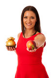 Woman deciding to eat healthy fruit or chocolate candy. Stock Image