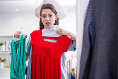 Woman deciding between two dresses Stock Photo