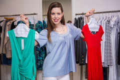 Woman deciding between two dresses Stock Image