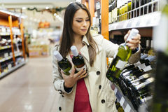 Woman deciding what wine to buy. And shopping in supermarket Stock Photography