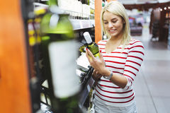 Woman deciding what wine to buy Royalty Free Stock Image