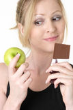 Woman deciding whether to eat apple or chocolate. Attractive blond caucasian woman holding an apple and chocolate bar trying to decide which one to eat smiling Stock Photos