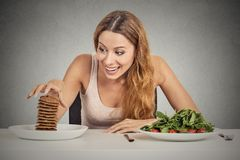 Woman deciding whether to eat healthy food or sweet cookies she craving. Portrait young woman deciding whether to eat healthy food or sweet cookies she is stock photography