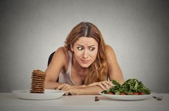 Woman deciding whether to eat healthy food or sweet cookies she craving Royalty Free Stock Images
