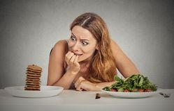 Woman deciding whether to eat healthy food or sweet cookies she craving. Portrait young woman deciding whether to eat healthy food or sweet cookies she is royalty free stock photography