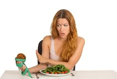 Woman deciding whether to eat healthy food or sweet cookies. Portrait young woman deciding whether to eat healthy food or sweet cookies she is craving sitting at Stock Photos