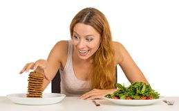 Woman deciding whether to eat healthy food or sweet cookies. Portrait young woman deciding whether to eat healthy food or sweet cookies she is craving sitting at royalty free stock photos