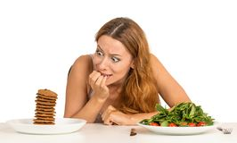 Woman deciding whether to eat healthy food or sweet cookies Royalty Free Stock Photography