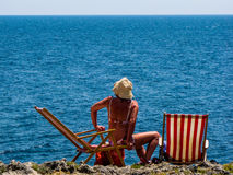 Woman on deckchair by the sea Stock Image