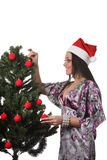 Woman decorate a christmas tree Royalty Free Stock Photo