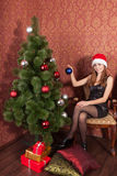 Woman decorate a christmas tree Stock Photos