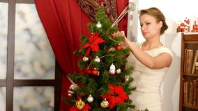 Woman decorate Christmas tree at home stock video footage
