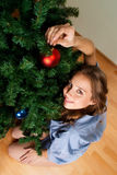 Woman decorate new year. Young woman decorate new year tree in domestic environment Stock Image