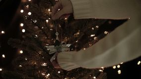 Woman decorate with star garland on Christmas tree with glow bokeh lights background.  stock video footage