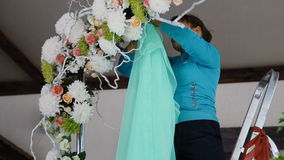 Woman decorate wedding arch with the green fabric stock video