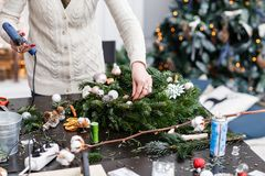 Woman decorated a Christmas wreath. Attaches toys and decor with glue gun. Hands close-up. Master class on making. Manufacturer of Christmas wreath from branches royalty free stock image
