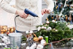 Woman decorated a Christmas wreath. Attaches toys and decor with glue gun. Hands close-up. Master class on making. Manufacturer of Christmas wreath from branches stock photography