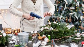 Woman decorated a Christmas wreath. Attaches toys and decor with glue gun. Hands close-up. Master class on making. Manufacturer of Christmas wreath from branches stock photo