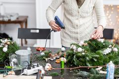 Woman decorated a Christmas wreath. Attaches toys and decor with glue gun. Hands close-up. Master class on making. Manufacturer of Christmas wreath from branches stock images