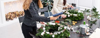 Woman decorated a Christmas wreath. Attaches toys and decor with glue gun. Hands close-up. Master class on making. Manufacturer of Christmas wreath from branches stock photos