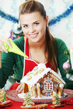 Woman decorated gingerbread house Stock Photos