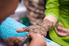 Traditional mehendi henna decoration. A woman is decorated with traditional henna mehendi designs during a Hindu wedding celebration stock image