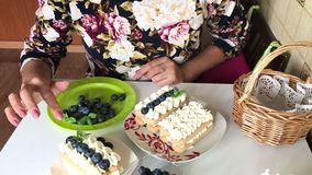 A woman decorates a cake with mint leaves. Corrects the leaves. Layers of savoiardi cookies and cream layers are decorated with
